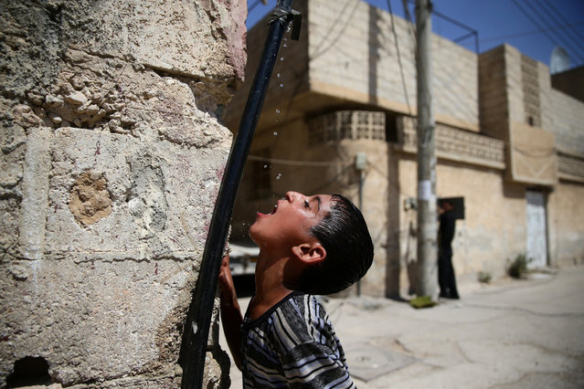 A boy drinks water from a pipe, in the rebel held besieged town of Douma, eastern Damascus suburb of Ghouta, Syria, June 23, 2016. (Photo by Bassam Khabieh/Reuters)