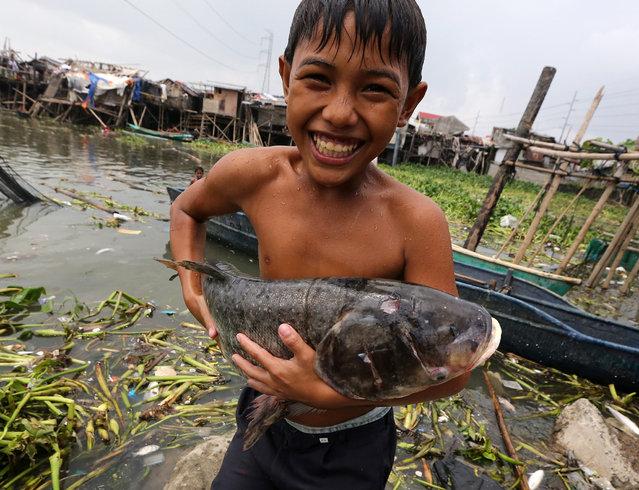 A Filipino boy carries a fish washed by flood at a lake in Muntinlupa city, south of Manila, Philippines, 18 July 2014. The strongest storm to hit the Philippines this year, typhoon Rammasun, killed 60 people and left nearly two million in the capital and eastern provinces without power officials said on 18 July, as a new storm threatened to bring more rains over the country's eastern provinces. (Photo by Francis R. Malasig/AFP Photo)