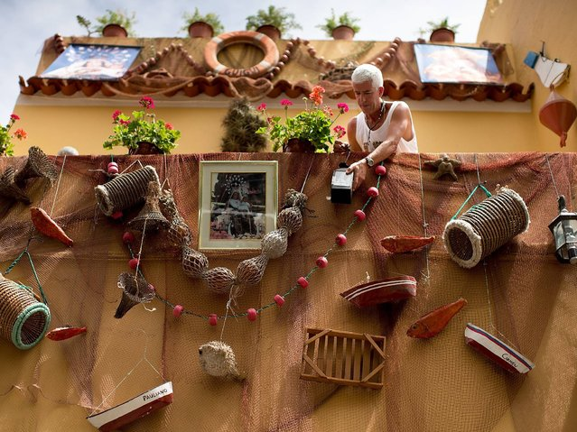 A man decorates his balcony with fishing objects surrounding a Virgen de la Cruz statue picture ahead of its procession in Puerto de la Cruz on the Canary island of Tenerife. (Photo by Gonzalo Arroyo Moreno/Getty Images)