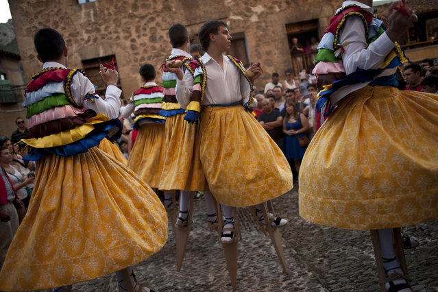 "Dancers perform on stilts in honor of Saint Mary Magdalene, in a street for the traditional ""Danza de Los Zancos"" (Los Zancos Dance), in the small town of Anguiano, northern Spain Tuesday, July 22, 2014. Eight young people from the town balance on stilts down the old street, turning to the sound of folk music played on a pipe and drum. (Photo by Alvaro Barrientos/AP Photo)"