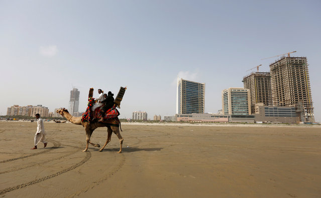 A family rides a camel past the construction of an office building and mall complex on Clifton beach  in Karachi, Pakistan, May 20, 2016. (Photo by Akhtar Soomro/Reuters)