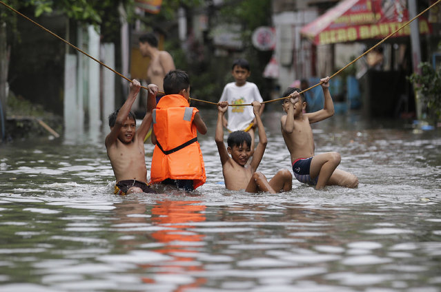 """Boys play outside their flooded homes after heavy rains from tropical storm """"Nesat"""" flooded parts of metropolitan Manila, Philippines on Thursday, July 27, 2017. Strong rains caused floods in low-lying areas and classes were suspended in most schools in the capital. (Photo by Aaron Favila/AP Photo)"""