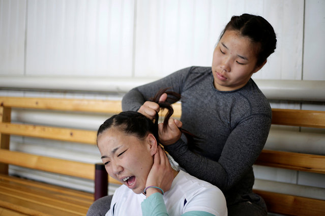 Mongolia's wrestler Oyuntuya Otgonbat reacts as her teammate Sarankhuhuo Erdenetuya ties her hair before a daily training session at the Mongolia Women's National Wrestling Team training centre in Bayanzurkh district of Ulaanbaatar, Mongolia, July 1, 2016. (Photo by Jason Lee/Reuters)