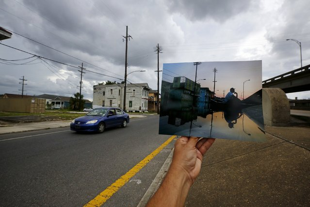 Photographer Carlos Barria holds a print of a photograph he took in 2005, as he matches it up at the same location 10 years on, in New Orleans, United States, August 18, 2015. The print shows Errol Morning sitting on his boat on a flooded street, September 5, 2005, after Hurricane Katrina struck. (Photo by Carlos Barria/Reuters)