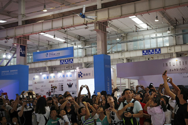 Visitors watch a remote-controlled dragonfly performing at the World Robot Conference at the Yichuang International Conference and Exhibition Centre in Beijing, Wednesday, August 23, 2017. (Photo by Andy Wong/AP Photo)