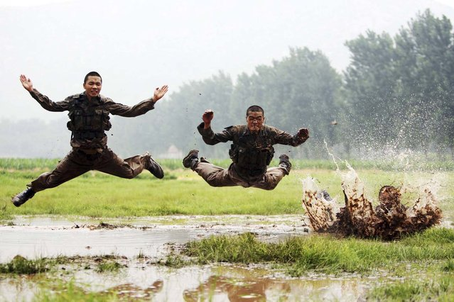 Soldiers jump as they take part during a military training session in muddy water at a military base in Jinan, Shandong province China, July 23, 2012. (Photo by China Daily/Reuters)