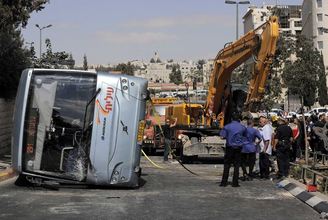 An overturned bus lies at the scene of a suspected attack in Jerusalem August 4, 2014. A construction vehicle hit and killed a pedestrian and overturned the bus on a main street in Jerusalem on Monday in what police suspect was a Palestinian attack, which ended when policemen shot dead the driver of the yellow excavator. (Photo by Ammar Awad/Reuters)