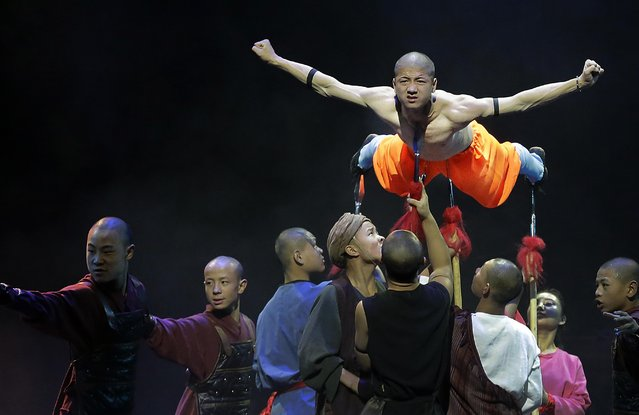 """A Shaolin monk is propped up by spears during a media preview of """"Shaolin"""" on Wednesday, July 13, 2016, in Singapore. The show """"Shaolin"""" combines traditional Shaolin kung fu and choreographed moves to music and is inspired by martial arts experts from the Shaolin Temple, said to be the birthplace of Kung Fu. (Photo by Wong Maye-E/AP Photo)"""