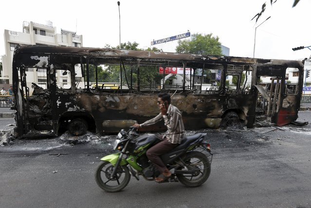 A man rides a motorcycle past the wreckage of a bus that was burnt in the clashes between the police and protesters in Ahmedabad, India, August 26, 2015. India deployed paramilitary forces and imposed a curfew in the western state of Gujarat on Wednesday after violence broke out at a protest led by a powerful clan to demand more government jobs and college places. (Photo by Amit Dave/Reuters)