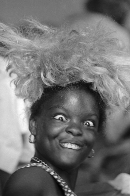 This young Miss takes time out for a bit of comedy as she tries on a blond wig she found in Salvation Army clothing center for hurricane Camille refugees at Gulfport, Miss., on August 25, 1969. (Photo by Joe Holloway/AP Photo)