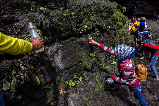 A picture made available on 21 July 2016 shows Indonesian Tenggerese Hindu worshipers collecting holy water at Widodaren cave as part of the Tenggerese Hindu Yadnya Kasada Festival in Probolinggo, East java, Indonesia, 20 July 2016. (Photo by Fully Handoko/EPA)
