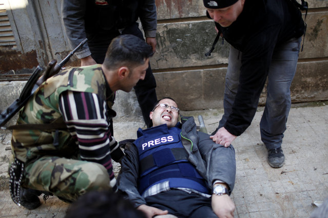 Ayman al-Sahili, a Reuters cameraman, reacts as he was shot in the leg while filming on the front line in Syria's north city of Aleppo by a sniper loyal to Syrian President Bashar el-Assad December, 31, 2012. (Photo by Ahmed Jadallah/Reuters)