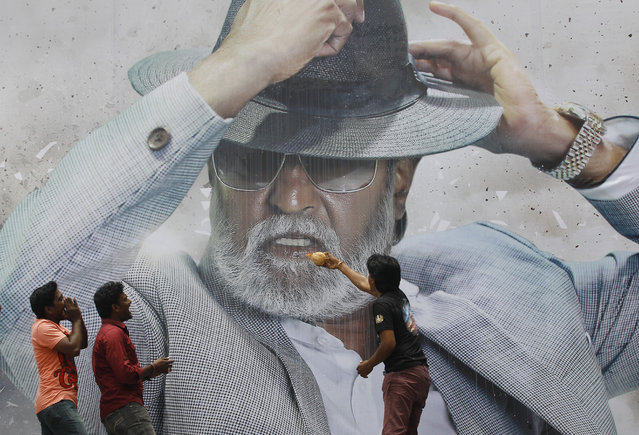 "Fans of Indian superstar Rajinikanth offer prayers in front of his poster outside a cinema hall to celebrate the screening of ""Kabali"" in Chennai, India, Friday, July 22, 2016. Hundreds of thousands of fans of Indian superstar Rajinikanth thronged cinemas across India and Malaysia on Friday for the premiere of his latest film, ""Kabali"", jumping from their seats and dancing in the aisles as their hero fought enemies in the gangster flick. (Photo by Aijaz Rahi/AP Photo)"