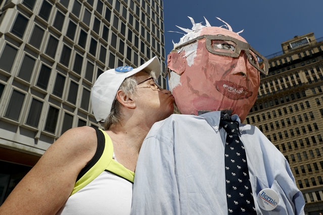 Sue Kirby poses for a picture with a larger-than-life Bernie Sanders, papier-mache head in Philadelphia, Wednesday, July 27, 2016, during the third day of the Democratic National Convention. Kirby, 65, built the doll about a year ago for Sanders rallies near home in Salem, Mass. She learned from a lifetime of activism that having a prop is a good way to get public (and media) attention. (Photo by Alex Brandon/AP Photo)
