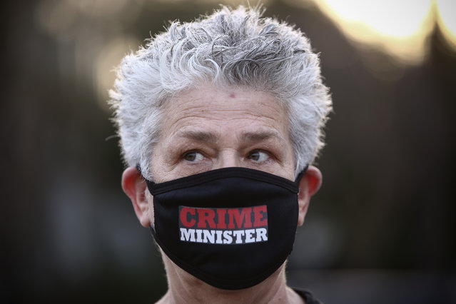 """A woman wears a protective face mask amid concerns over the country's coronavirus outbreak, take part in a protest against Prime Minister Benjamin Netanyahu in Tel Aviv, Israel, Sunday, April 19, 2020. More than 2,000 people took to the streets on Sunday, demonstrating against Prime Minister Benjamin Netanyahu's attempts to form an """"emergency"""" government with his chief rival and accusing him of using the coronavirus crisis to escape prosecution on corruption charges. (Photo by Oded Balilty/AP Photo)"""