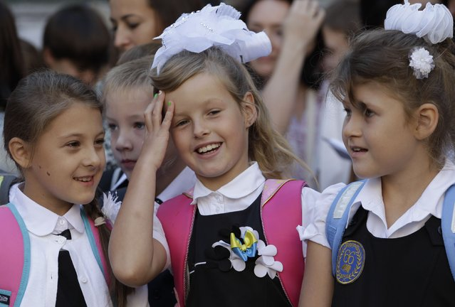 Schoolgirls talk during morning assembly in a school in the southern coastal town of Mariupol, September 1, 2014. (Photo by Vasily Fedosenko/Reuters)