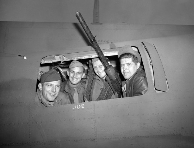 Four members of the crew that accompanied General Ira Eaker when he led the All-American bombing flight on German held Rouen, August 17, 1942, smile from the waist-gun port after their safe return. (Photo by AP Photo)