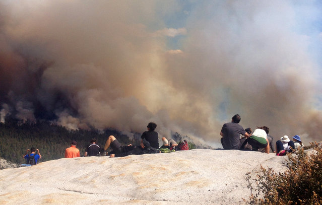 In this Sunday, September 7, 2014, photo provided by Rachael Kirk, climbers view a wildfire from the top of Half Dome in Yosemite National Park, Calif. (Photo by Rachel Kirk/AP Photo)