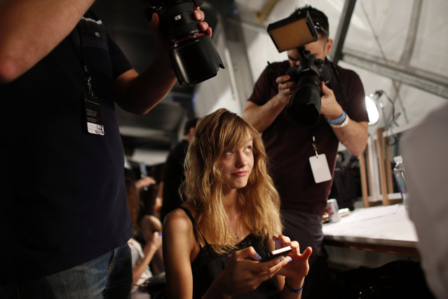 Fashion model Yulia Musieichuk of Kiev, Ukraine, reacts as she is photographed from multiple angles while having her toenails painted backstage before the Rebecca Minkoff Spring 2015 collection show Friday, September 5, 2014, during Fashion Week, in New York. Musieichuk, 22, who was scouted in her native Ukraine at age 16, has a mother, father, sister and nephew back home. (Photo by Jason DeCrow/AP Photo)