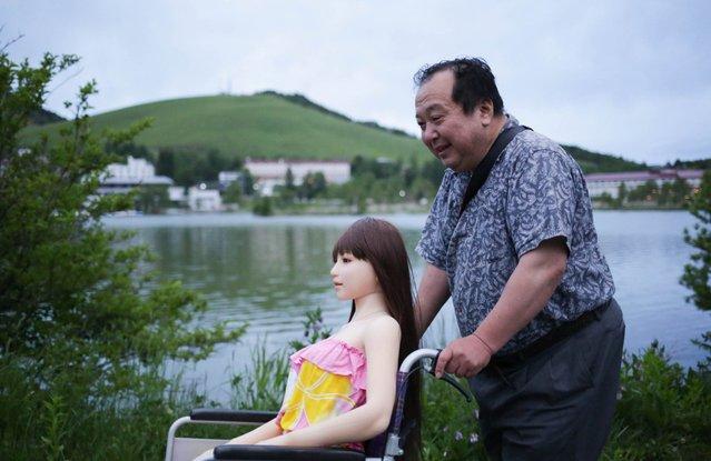 """Senji Nakajima takes a walk with his Love Doll """"Saori"""" at lake Suwa on June 4, 2016 in Nagano, Japan. (Photo by Taro Karibe/Getty Images)"""
