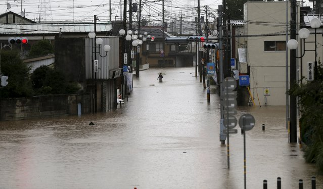 A man wades through a local shopping area flooded by the Kinugawa river, caused by typhoon Etau, in Joso, Ibaraki prefecture, Japan, September 10, 2015. (Photo by Issei Kato/Reuters)
