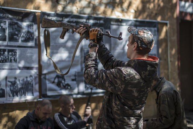 A pro-Russian rebel checks his rifle inside the Vostok (East) battalion base in Donetsk, eastern Ukraine, September 17, 2014. (Photo by Marko Djurica/Reuters)