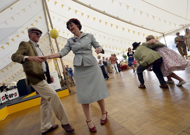 Visitors and car enthusiasts dance at the Goodwood Revival historic motor racing festival in Goodwood, near Chichester in south England, Britain, September 11, 2015. (Photo by Toby Melville/Reuters)