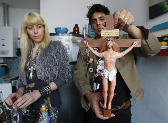 "Artist Emiliano Paolini (R), and his partner Marianela Perelli, show their ""Ken"" doll that they have re-designed into the religious figure of Jesus Christ at their workshop in Rosario, north of Buenos Aires September 23, 2014. (Photo by Enrique Marcarian/Reuters)"