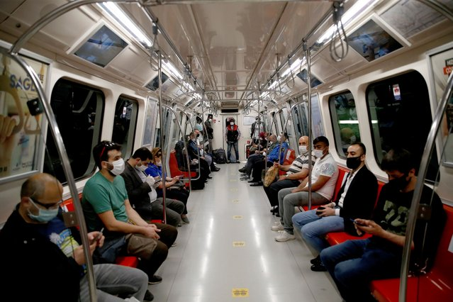 People observe social distancing on a metro carriage in Istanbul, a few hours before the weekend lockdown because of the coronavirus, Friday, May 15, 2020. Teenagers were able to leave their homes for the first time in 42 days on Friday, as their turn came for a few hours of respite from Turkey's coronavirus lockdowns. Turkey has subjected people aged 65 and over and those younger than 20, to a curfew for the past several weeks. (Photo by Emrah Gurel/AP Photo)