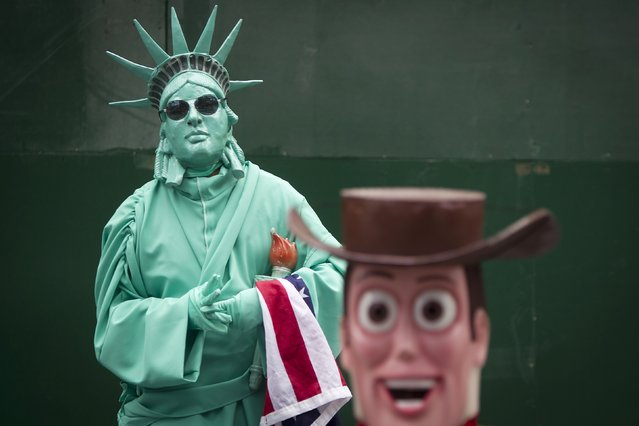 People, who dress up as the Statue of Liberty and Woody from the Toy Story film, to pose with people for tips, stand in Times Square in the Manhattan borough of New York September 29, 2014. (Photo by Carlo Allegri/Reuters)