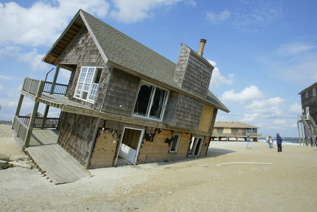 A house that was slammed off its foundation by Hurricane Isabel sits precariously on the beach one month after it hit Rodanthe, North Carolina October 18, 2003. (Photo by Rick Wilking/Reuters)