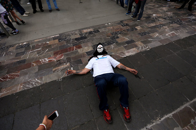 Mexican wrestler known as Parka rests on the floor during the annual pilgrimage to the Basilica of Our Lady Guadalupe in Mexico City, Mexico August 25, 2016. (Photo by Carlos Jasso/Reuters)