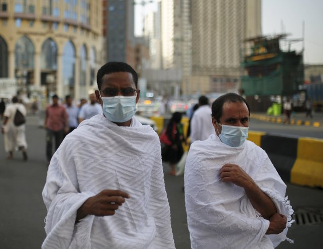 Muslim pilgrims wear protective masks as they walk on a road in the holy city of Mecca ahead of the annual haj pilgrimage September 21, 2015. (Photo by Ahmad Masood/Reuters)