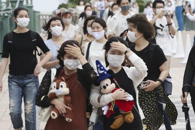 People wearing face masks to protect against the spread of the new coronavirus walk toward the entrance to Tokyo Disneyland in Urayasu, near Tokyo, Wednesday, July 1, 2020. (Photo by Koji Sasahara/AP Photo)