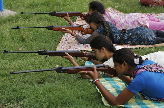 Girls practise with air rifles during a weapons training course as part of an eight-day training programme organized by the Bajrang Dal, a hardline Hindu group, inside a school premises on the outskirts of Jammu July 21, 2010. (Photo by Mukesh Gupta/Reuters)