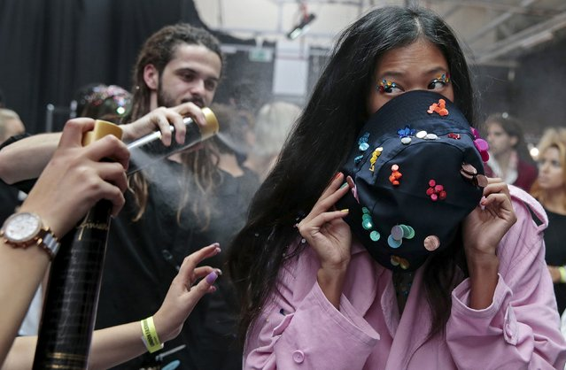 A model uses a hat to cover her face as stylists apply hairspray backstage before the Ashish Spring/Summer 2016 collection during London Fashion Week in London, Britain September 22, 2015. (Photo by Suzanne Plunkett/Reuters)