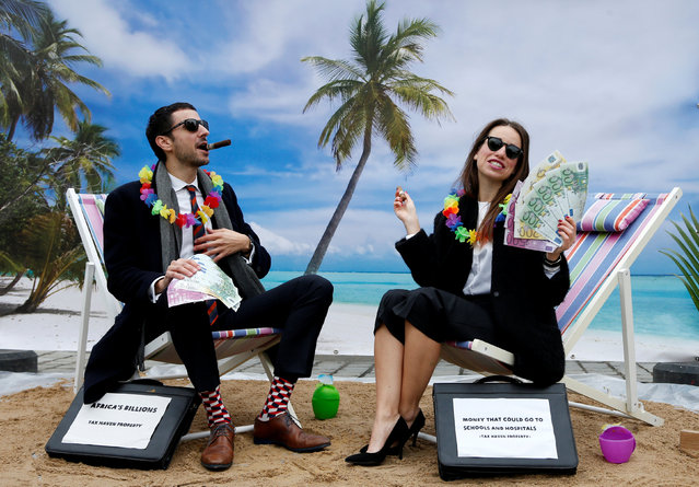 Activists stage a protest on a mock tropical island beach representing a tax haven outside a meeting of European Union finance ministers in Brussels, Belgium, December 5, 2017. (Photo by Francois Lenoir/Reuters)