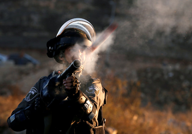 "An Israeli border policeman reacts as he fires towards Palestinian protesters during clashes as Palestinians call for a ""day of rage"" in response to U.S. President Donald Trump's recognition of Jerusalem as Israel's capital, near the Jewish settlement of Beit El, near the West Bank city of Ramallah December 8, 2017. (Photo by Mohamad Torokman/Reuters)"