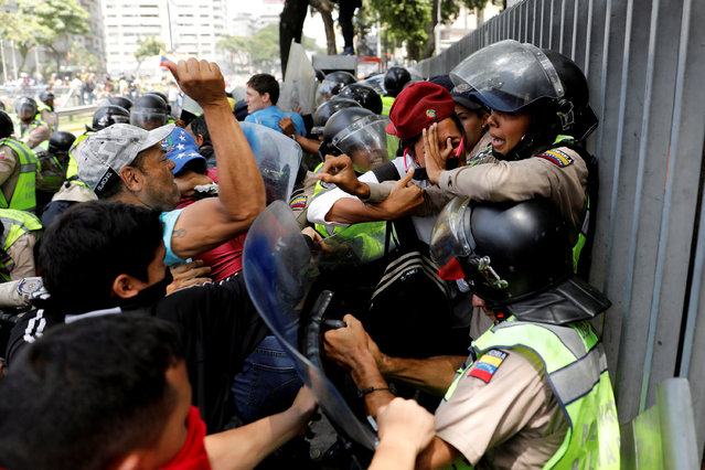 """Demonstrators scuffle with security forces during an opposition rally in Caracas, Venezuela, April 4, 2017. Venezuelan security forces quelled masked protesters with tear gas, water cannons and pepper spray in Caracas after blocking an opposition rally against socialist President Nicolas Maduro. The clashes began after authorities closed subway stations, set up checkpoints and cordoned off a square where opponents had planned their latest protest against the government and the crippling economic crisis. Carlos Garcia Rawlins: """"For me that was the day that made a difference, never before had I seen the protesters and police clashing men-to-men and struggling back and forward. From then, the strategy of the police changed and they never faced the protesters so close again"""". (Photo by Carlos Garcia Rawlins/Reuters)"""