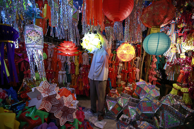 A vendor hangs a lantern for sale at a Diwali market in Mumbai October 20, 2014. (Photo by Danish Siddiqui/Reuters)