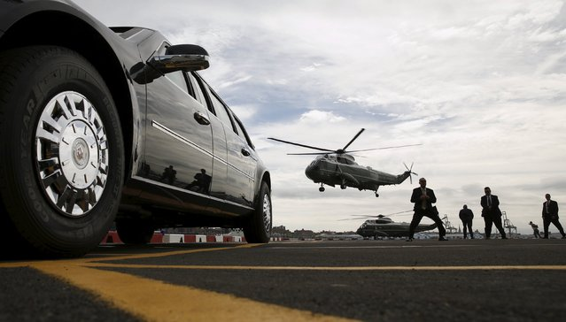 Marine One lands while Secret Service agents brace themselves against the prop wash beside the presidential limo as U.S. President Barack Obama arrives at the Wall St. Heliport in New York September 27, 2015. Obama arrived in New York to attend the United Nations General Assembly. (Photo by Kevin Lamarque/Reuters)