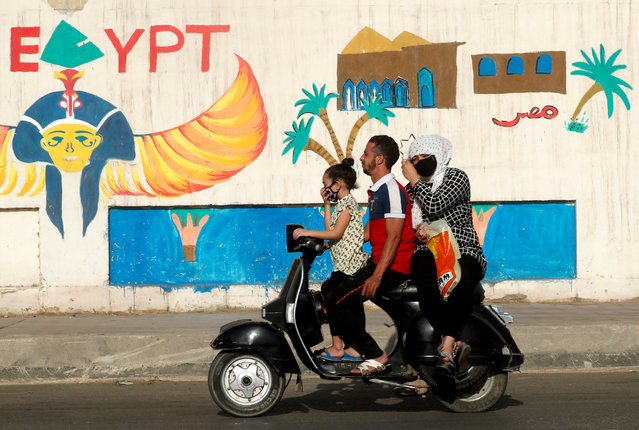 A man rides a motorcycle with his family next to a wall with pharaonic images painted on it, as the spread of the coronavirus disease (COVID-19) continues, in Cairo, Egypt on June 4, 2020. (Photo by Amr Abdallah Dalsh/Reuters)