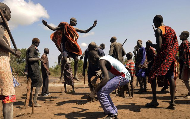 Cattle keepers from the Dinka tribe perform a traditional dance after a prayer session for peace and good health along the route to Rajaf Payam outside the capital Juba October 18, 2014. (Photo by Jok Solomon/Reuters)