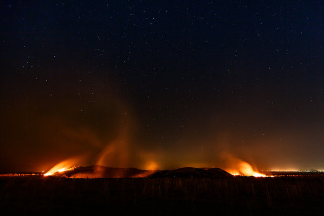 """Smoke snakes"". At end of summer, farmers burn their crops to provide nutrients to the soil for the next season. At night, this agricultural procedure became an impressive spectacle as these fires could spread over dozens of meters and produce a lot of smoke. As there is just minor light pollution, I waited until the stars could be seen again. Photo location: Iraqi Kurdistan, Iraq. (Photo and caption by Juan Aguilar/National Geographic Photo Contest)"