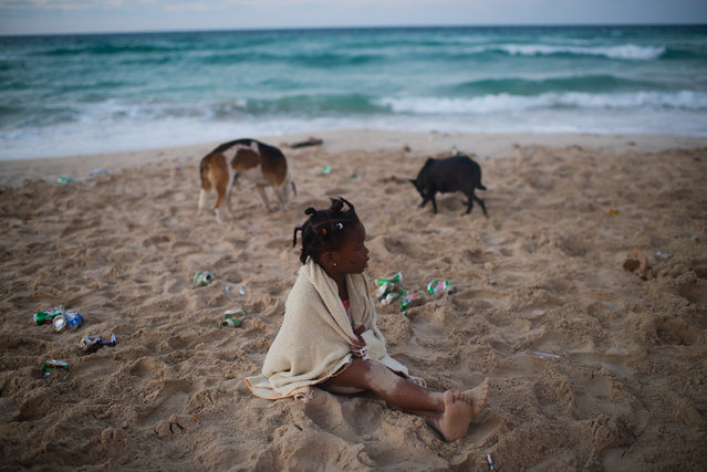 Four-year-old Estefany Gloria Garcia sits on the littered shore of Santa Maria beach, which is about 15 miles from Havana. Her mother was partying with her friends. It is the closest beach to Havana. The government is demolishing buildings all over the coast of East Havana and recovering and restoring beach dunes. (Photo by Sarah L. Voisin/The Washington Post)