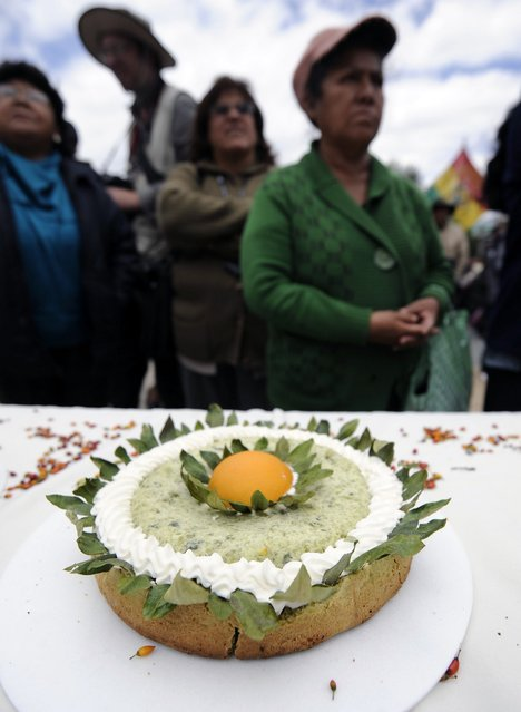 """Women stand next to a pie made with coca flour during a celebration for the reincorporation of Bolivia to the UN Convention Against Illicit Traffic in Narcotic Drugs in La Paz on January 14, 2013. """"The coca leaf is not any more seen as cocaine (..), it is a victory of our identity"""" said Bolivian President Evo Morales. AFP PHOTO/Jorge Bernal        (Photo credit should read JORGE BERNAL/AFP/Getty Images)"""