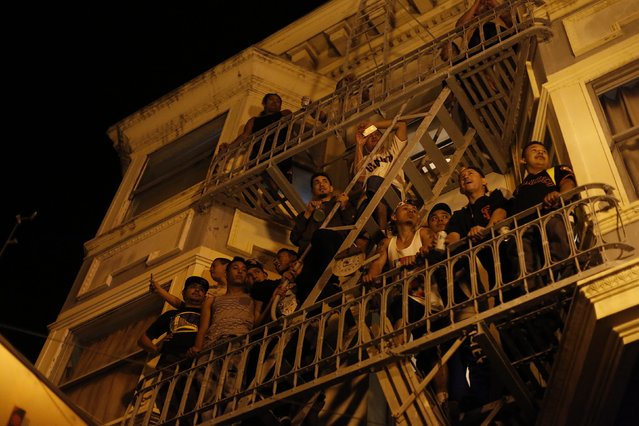 People watch a street celebration from a balcony in San Francisco, California October 29, 2014. (Photo by Stephen Lam/Reuters)