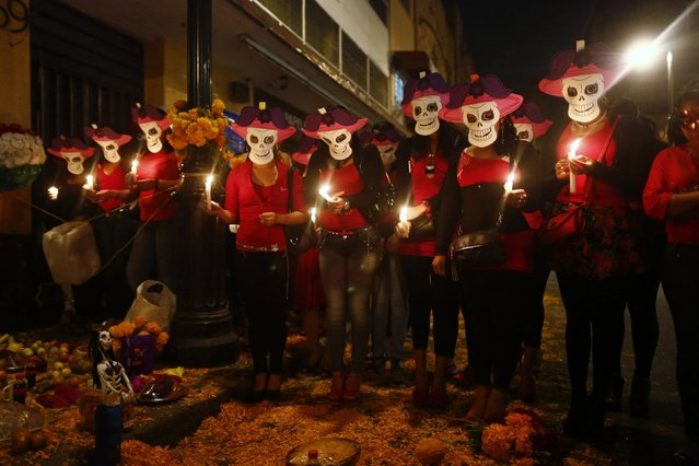 s*x workers wear skeleton masks, a traditional Mexican symbol representing the Day of the Dead, as they make an offering during a procession to remember their deceased colleagues, especially those who were violently murdered, in Mexico City October 27, 2014. The annual Day of the Dead is observed on November 1 and 2. (Photo by Edgard Garrido/Reuters)