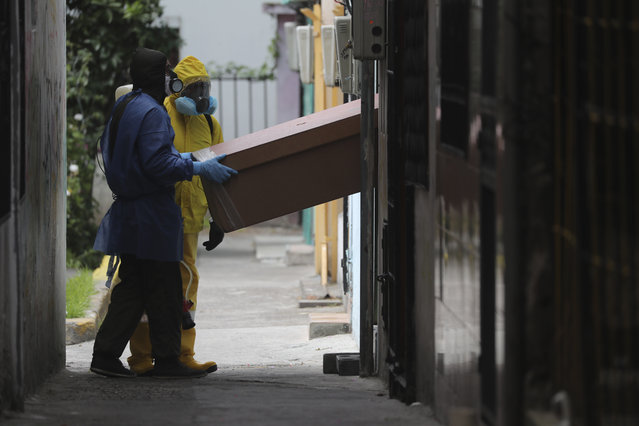 Funeral workers remove the body of a person who is suspected to have died from symptoms related to the new coronavirus, in Quito, Ecuador, Friday, August 14, 2020. The numbers of those infected with COVID-19 have been rising in the capital. (Photo by Dolores Ochoa/AP Photo)