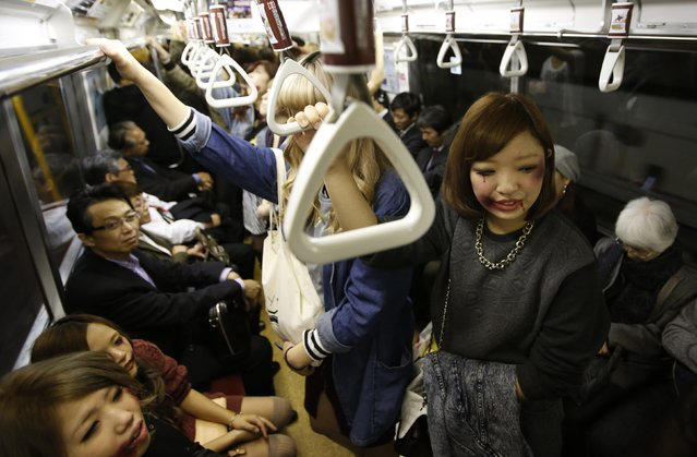 """Participants wearing costumes and make-up as zombies ride a subway after a Halloween event to promote the U.S. TV series """"The Walking Dead"""" in Tokyo October 31, 2013. More than a thousand people dressed as zombies participated in the event to simulate taking over Tokyo Tower, according to organisers. (Photo by Issei Kato/Reuters)"""
